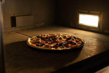 A round large pizza is baked in the oven with light. The cheese is melting. Pizzeria. Wall mural