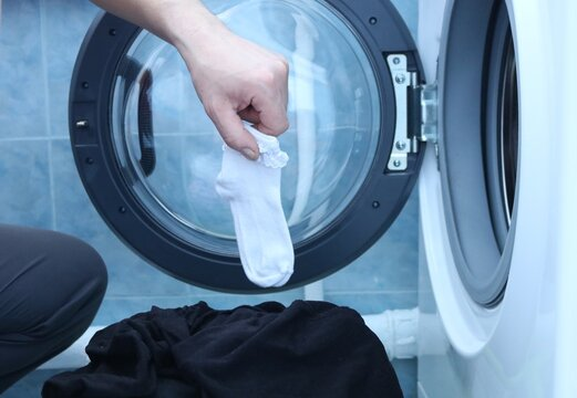 a man's hand holds a white children's sock with circles caught in washed black underwear, a man in a home laundry washed his clothes incorrectly, a comical surprise situation