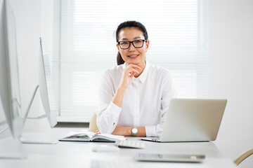 Asian business woman smiling at camera in an office