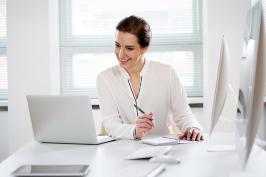 Portrait of business woman looking at camera at workplace in an office