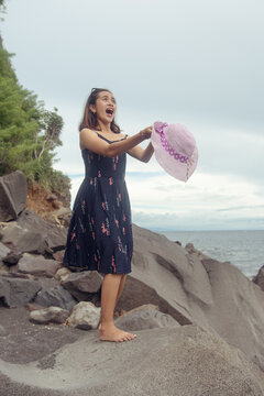"""Beach photoshoot with a beautiful balines girl on the beach """"Pantai bias lantang, Bali"""" with fashion hat and surprise."""