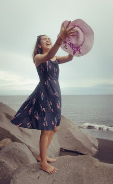 """Beach photoshoot with a beautiful balines girl on the beach """"Pantai bias lantang, Bali"""" with fashion hat and laughing."""