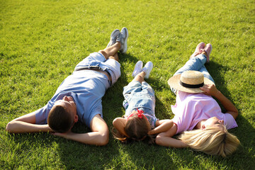 Happy parents with their child lying on green grass. Spending time in nature