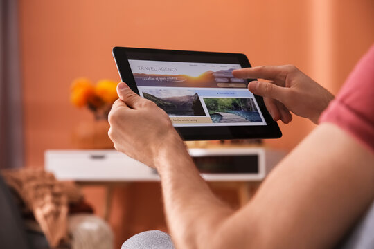 Man with tablet booking tickets online at home, closeup. Travel agency concept