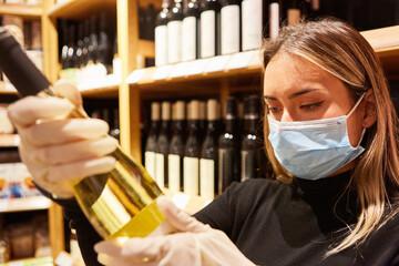 Kundin mit Maske wegen Covid-19 in einer Vinothek
