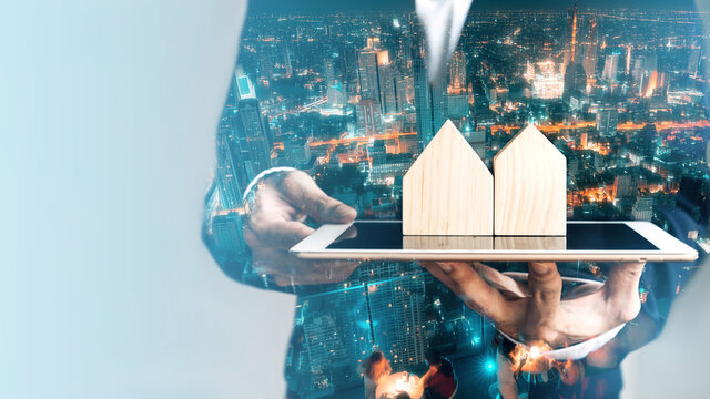Business realtor man holding digital tablet with home model double exposure with modern night city.