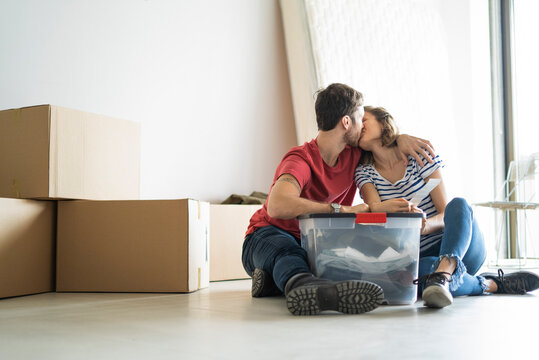 Young couple kissing in their new house