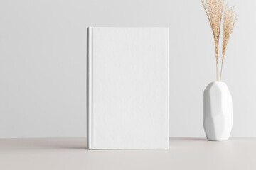 White book mockup with a dried grass in a vase on a beige table.