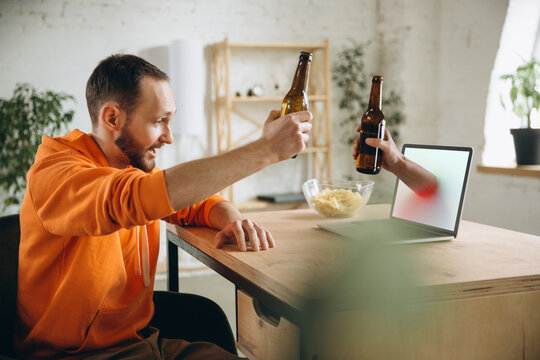 Friend. Young man drinking beer during meeting friends on virtual video call. Distance online meeting, chat together on laptop at home. Concept of remote safe meetings and entertainment.