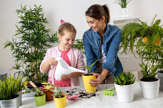 Mother advising her daughter how to water a plant in the pot