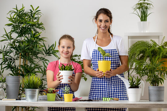 Mother and her daughter bonding in their apartment by doing some planting in flowerpots