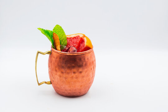 Cocktail with ice in a copper glass on a white background