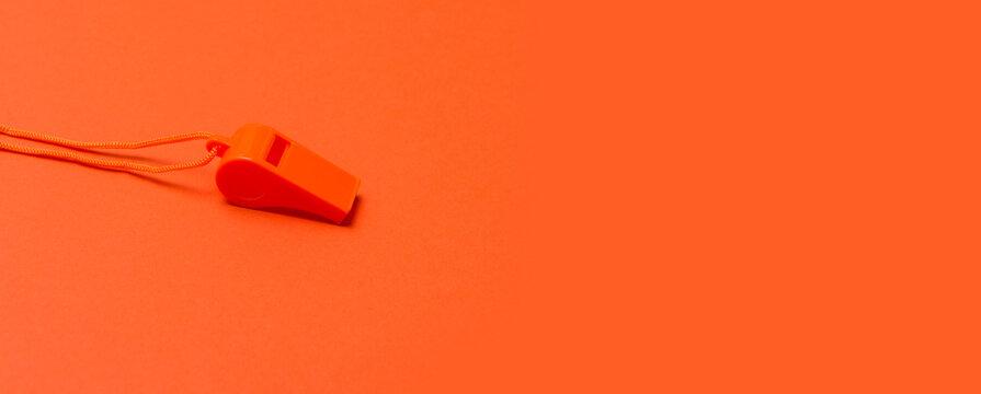 Orange sports whistle on orange background.Concept- sport compet