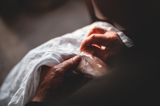 Female holds a needle in her hands and embroiders a pattern with white threads on a white cloth
