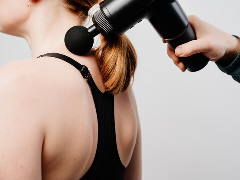 woman uses massage gun. medical-sports device helps to reduce muscle pain after training, helps to relieve fatigue, affects problem areas of body, improves condition of skin.
