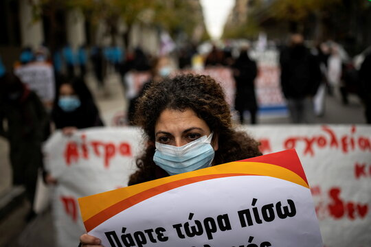 A primary school teacher wearing a protective face mask, holds a placard during a demonstration outside the Health Ministry, demanding enhanced safety measures in schools against the coronavirus disease (COVID-19), in Athens