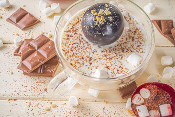 Hot chocolate bomb, with marshmallow and chocolates and nuts,  Woman's hand dropping chocolate bomb into cup with milk.