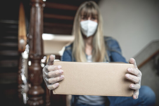 Dispatch postman bring parcels and post in covid 19 quarantine to the front home door with a face mask ffp 2 and protection gloves