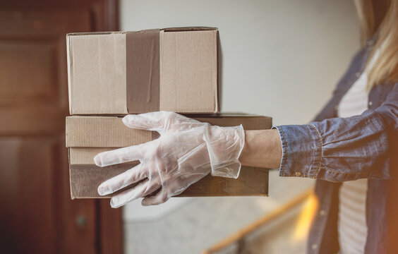Delivery services courier during the Coronavirus (COVID-19) pandemic, close-up of cardboard box holding by a courier wearing