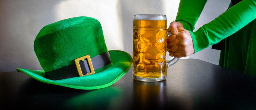St Patricks day glass beer hand hold costume hat leprechaun black background