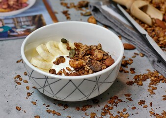 Wall Mural - Homemade cocoa granola in white bowl with cashew, almond and seeds on wooden background