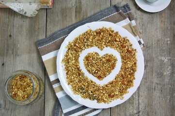 Wall Mural - Homemade granola in white bowl with almond and seeds on wooden background