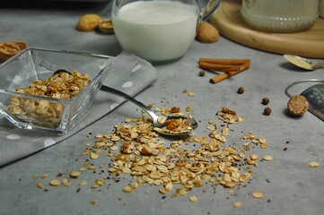 Wall Mural - Homemade granola in white bowl with almond and seeds on grey background