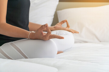 Midsection Of Woman Meditating On Bed At Home