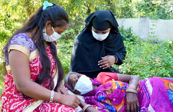 Horizontal shot of young Indian women taking care of another old sick woman