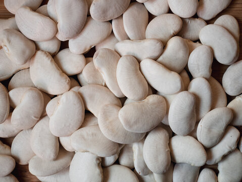 Top view of raw lima beans on a wooden table in the kitchen