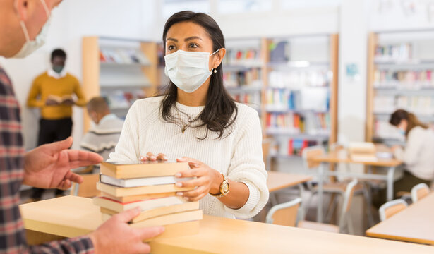 Hispanic woman in protective face mask talking to librarian while returning books to university library. Social distancing and precautions in coronavirus pandemic..