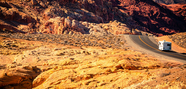A white motor home disappears over a ridge of red rocks in Valley of Fire State Park, northeast of Las Vegas, Nevada.