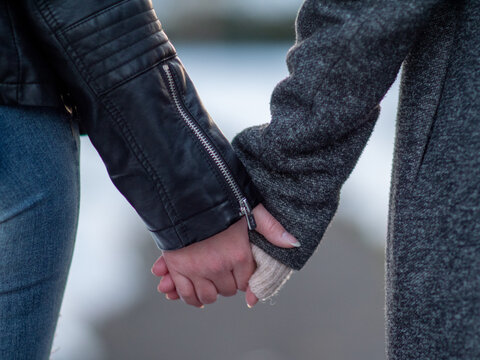 Two young women hold hands.