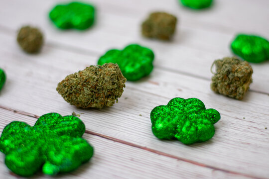 Cannabis Nugs Next to Glitter Covered Four Leaf Clovers