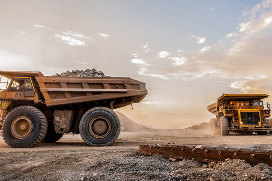 Trucks loaded with crushed rock fragments for transporting in platinum mining open pit, South Africa