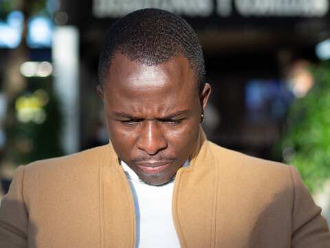 Shallow focus of an adult African male wearing a beige coat outdoors under the sunlight