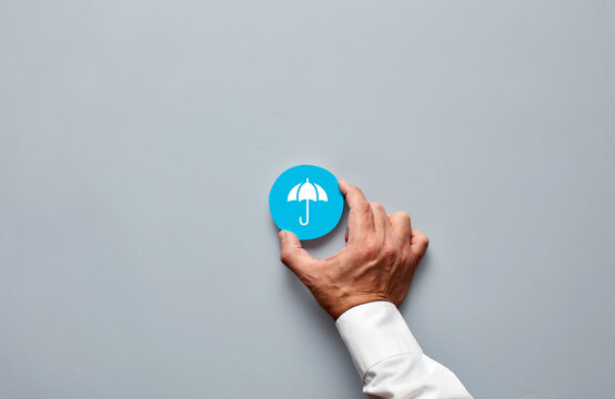 Businessman hand holding a blue badge with an umbrella icon representing insurance and protection.