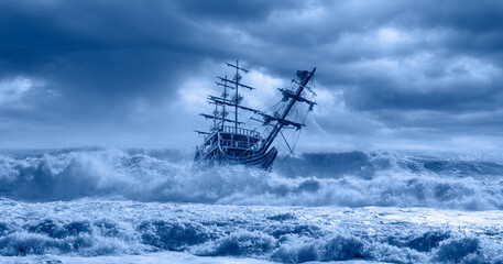Sailing old ship in a storm sea in the background stormy clouds