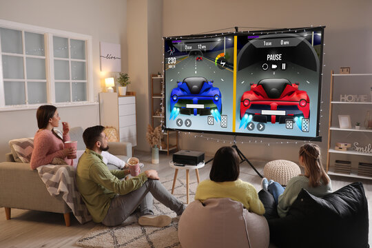 Friends playing video games on big screen at home
