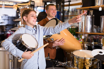 young father and teenage son examining drum units in guitar shop