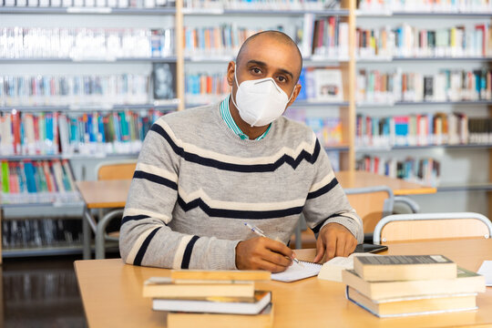 Focused Latin American adult wearing protective face mask looking for information in books in public library. New normal in coronavirus pandemic..