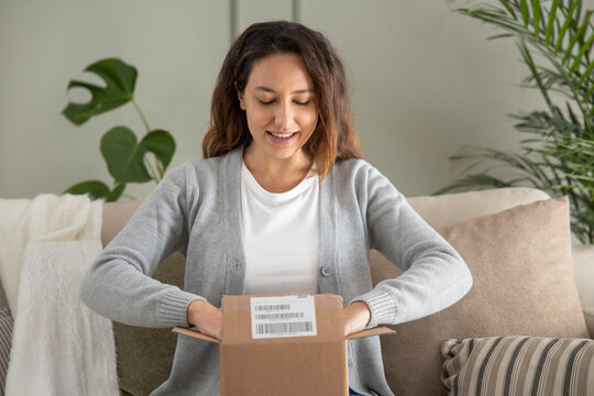 Woman opening personal online shopping parcel. Online shopping at home