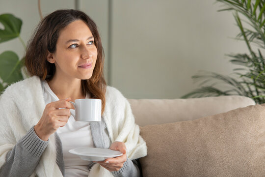 Cheerful young woman enjoying cup of coffee at home