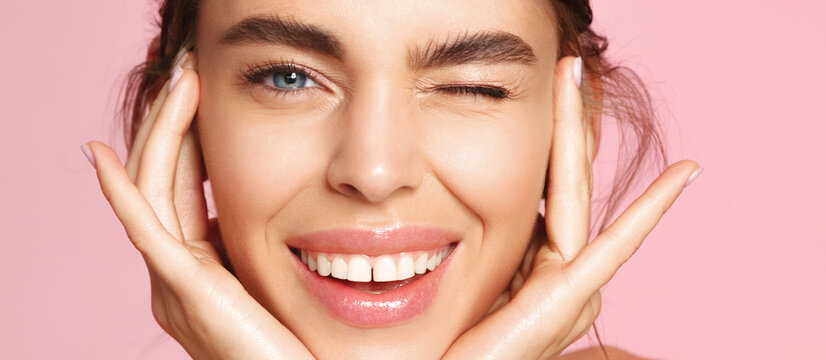 Skincare and beauty. Close up of smiling young woman winking at camera, touching shiny healthy skin, nourished face after tea tree and lemon facial serum and moisturizer, pink background