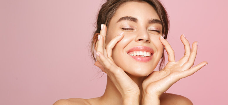 Skin care. Woman with beauty face touching healthy facial skin portrait. Beautiful smiling girl model with natural makeup touching glowing hydrated skin on pink background closeup