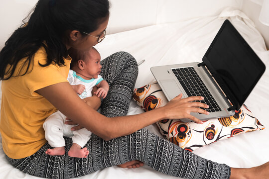 Young Hispanic mother with a baby working from home