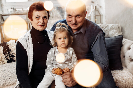 Portrait of loving grandparents with adorable baby girl. Mature man and woman with little granddaughter sit on the sofa, cuddling and smiling. Joyful family spend time together, happiness concept