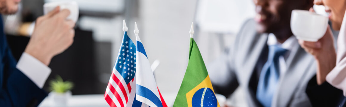selective focus of american, brazilian and usa flags near multicultural businesspeople drinking coffee on blurred background, partial view, banner