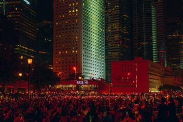 Fototapeta People On Illuminated Road Amidst Buildings At Night obraz
