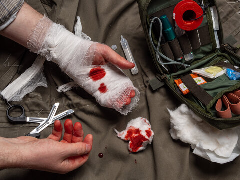 Bandaging process. First aid kit and items for stopping bleeding